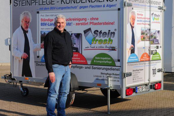 Mann steht vor einem Anhänger mit viel Werbung.